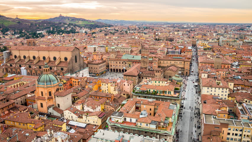 Aerial view of Bologna, Italy at sunset. Colorful sky over the historical city center with car traffic and old buildings. Time-lapse
