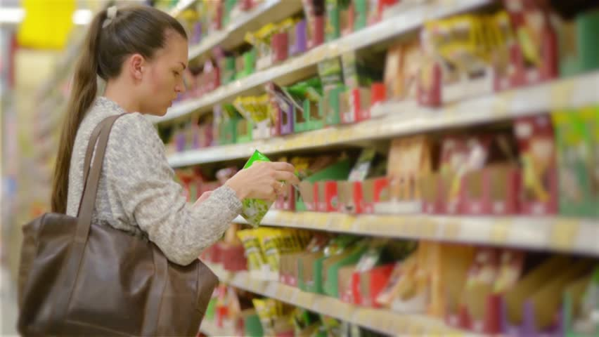 Young woman choosing spices in grocery store, beautiful woman shopping in a supermarket | Shutterstock HD Video #17630332