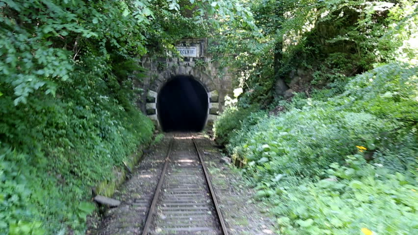 Back view of railroad train that entering a dark and old mountain tunnel. Inaugurated in 1863, it is the oldest mountain railway in Romania. Route between Oravita and Anina. Banat region.