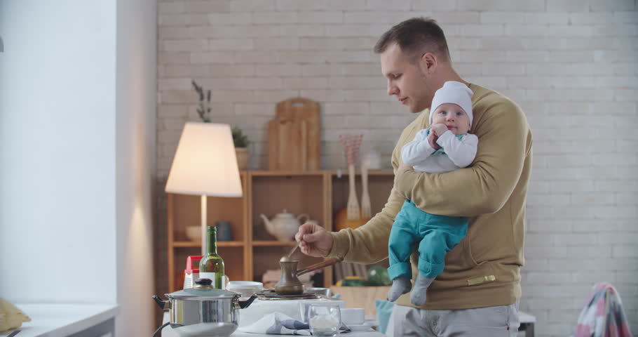 Father holding little baby and brewing coffee on stove in the kitchen whiles his wife coming and embracing them