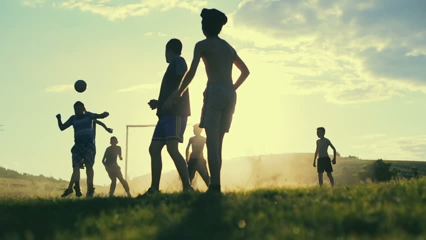 Boys are playing football in the sunshine day. Happy childhood and football in the village. Slow motion. #17646232