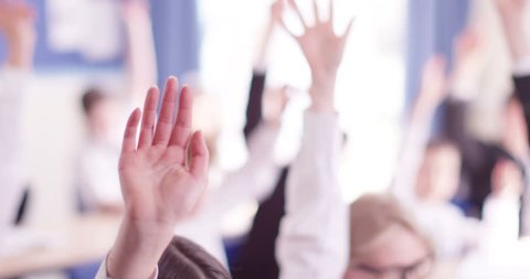 4k, students in class with their arm raised to answer a question. Slow motion.