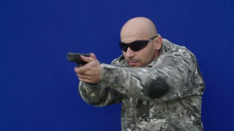 Man with a gun training on chroma key blue screen background