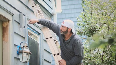 Handsome young man on ladder painting house exterior with paint roller