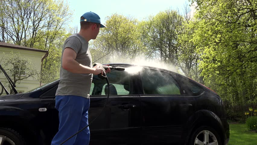 Manual car washing under high pressured water stock footage video man hosing his car at do it yourself car wash using high pressure water solutioingenieria Image collections