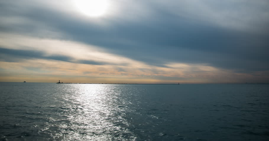 Chicago, Illinois, USA - view from Navy Pier facing Lake Michigan with lighthouse and boats after sunrise - Timelapse with zoom out