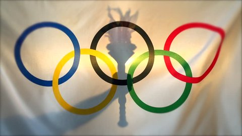 RIO DE JANEIRO - FEBRUARY 26, 2016: Silhouette of hand holding sport torch behind the rings of an Olympic flag  in anticipation of the city hosting the Summer Games.