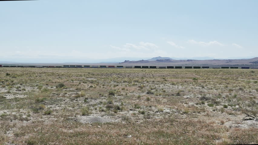 GREAT BASIN DESERT, WESTERN UTAH - JUNE 2016: POV-Side window driving view of a far distant train running parallel to road in a vast empty desert. | Shutterstock HD Video #17763142
