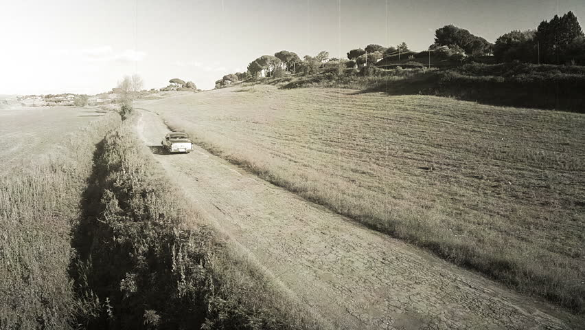 Car vintage effect 8mm, with aerial drone. N The camera follows the machine. Black and white  #17768941