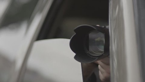 Spy, paparazzi or detective in the car,shooting on camera.