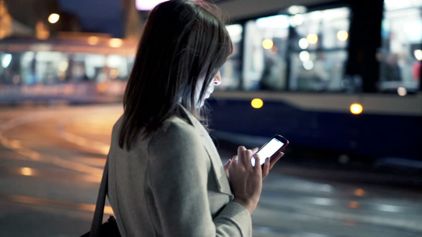 Young woman using smartphone and crossing street in city at night