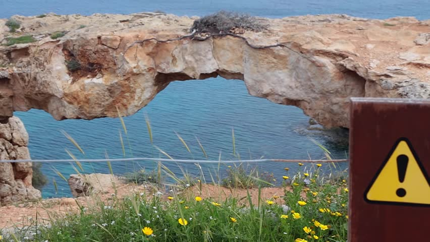 Cavo Greco, Cyprus March 2015. Lover's Bridge. Natural bridge in Cavo Greco (Cape Greco) National Forest Park. Warning sign | Shutterstock HD Video #17803222