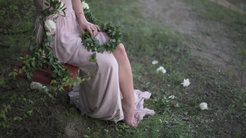 Young woman dressed in light pinc tunic playfully exposing her leg, sitting on decorated with flowers swing | Shutterstock HD Video #17809531