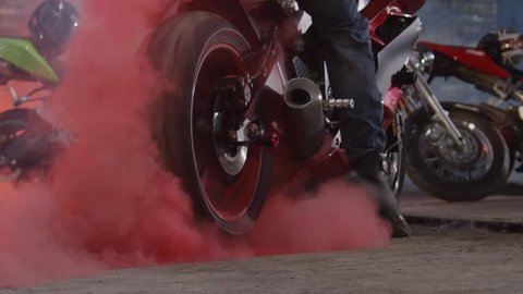 Super sport motorcycle doing a tire burnout with colorful sand, holi. Shot on RED EPIC Cinema Camera in slow motion.