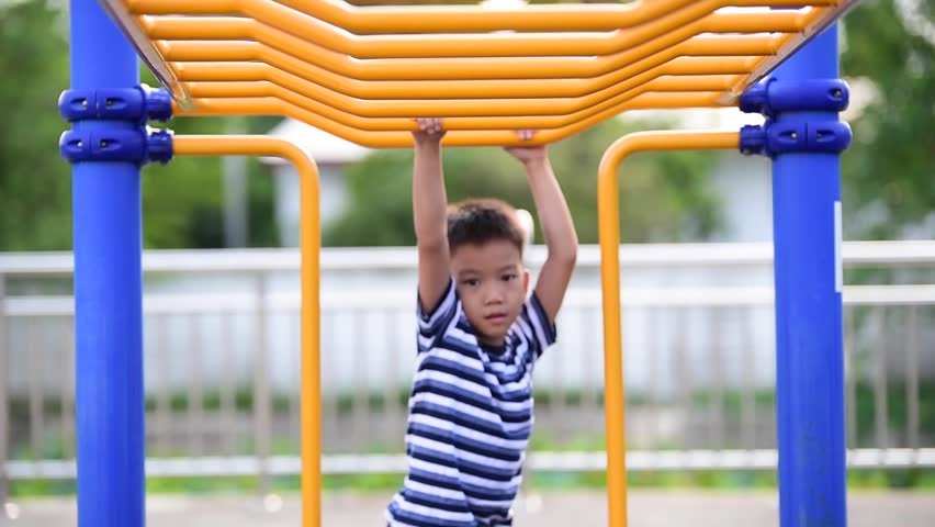 A Young Boy Hangs Upside Down On A Playground Monkey Bars -2073