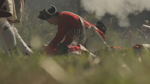VIRGINIA - OCTOBER 2014 - Reenactment, large-scale, epic American Revolutionary War anniversary recreation -- British Army Redcoat Soldiers march into battle with flags, cannons, muskets and horses