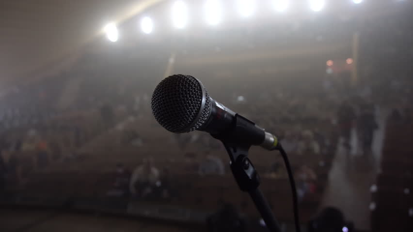 Auditorium in the Haze, a Large Plan of the Microphone on Stage, Spotlight, Backlight, People Gather in the Hall and Sit on Seats, Waiting For Performances, 4k | Shutterstock HD Video #17870185