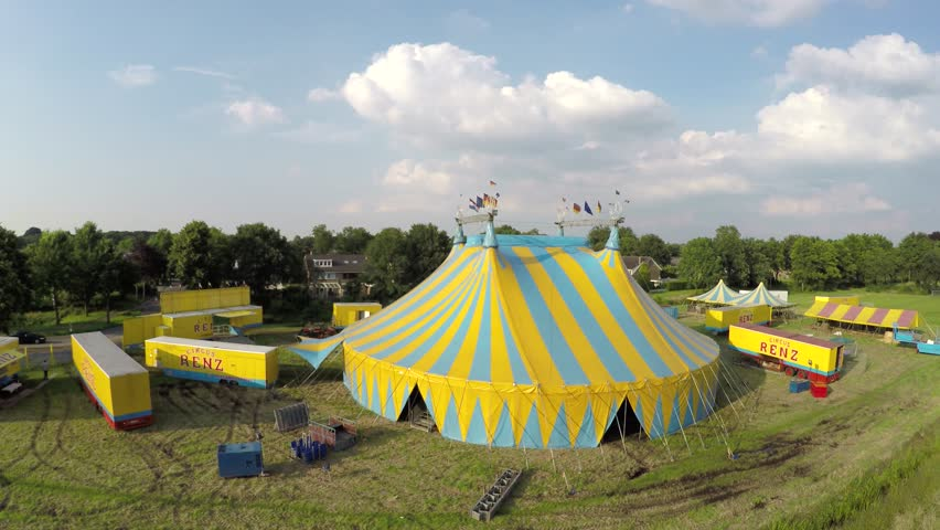 Aerial circling around circus tent colored in blue and yellow stripes also showing circus trucks and smaller tents and buildings on top of structure some flags are placed moved by wind 4k resolution