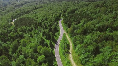 4K Cinematic drone shot - flying over a road / Discovering a road in the middle of a beautiful forest - with cars moving