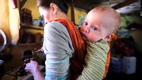 Mother is carrying her son on her back in sling while cooking. Chachzaevka Ecovillage. Altai mountains, Siberia, Russia.