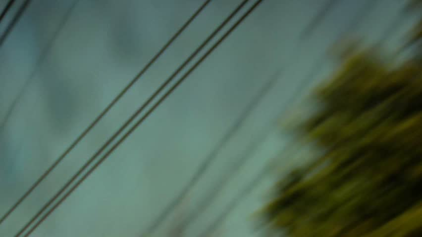 Passenger view of wires from a moving train. Daydreaming feel of passing time