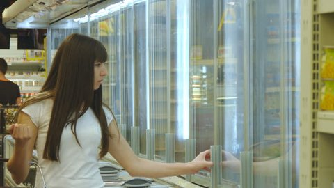 Young woman with shopping cart buying dairy or refrigerated groceries at the supermarket in the refrigerated section opening glass door. Girl coming up to the fridge in shop and taking product from it