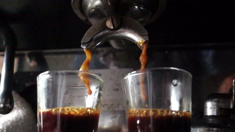 Closeup prepare double shot of espresso coffee, slow motion