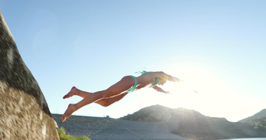 Young Woman Diving Into Lake At Sunset