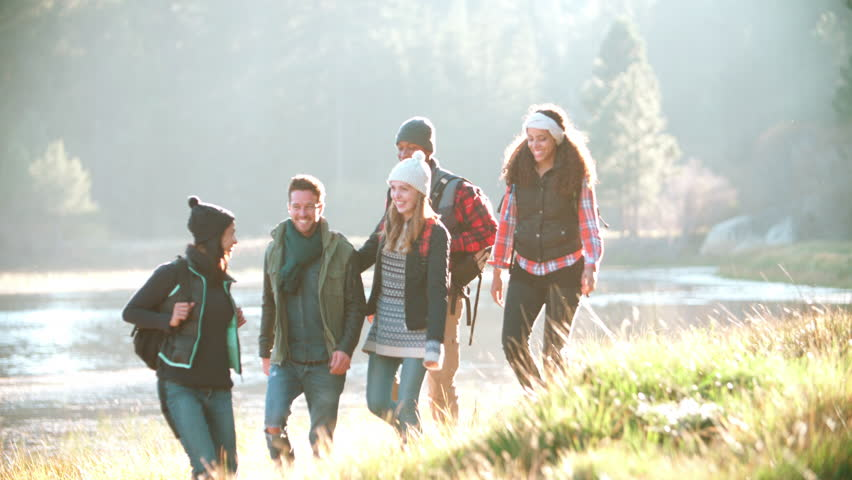 Five friends on a camping trip walking in a row near a lake