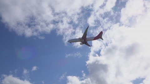SLOW MOTION CLOSE UP: Commercial airplane jet flying over the sun, landing. White and red plane flying over electric installation, departing from airport and distancing in beautiful blue skies