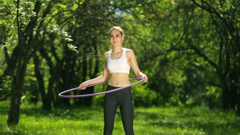 Portrait of beautiful young woman doing hula hoop, outdoors in the park. Woman rotates hula hoop on nature background.