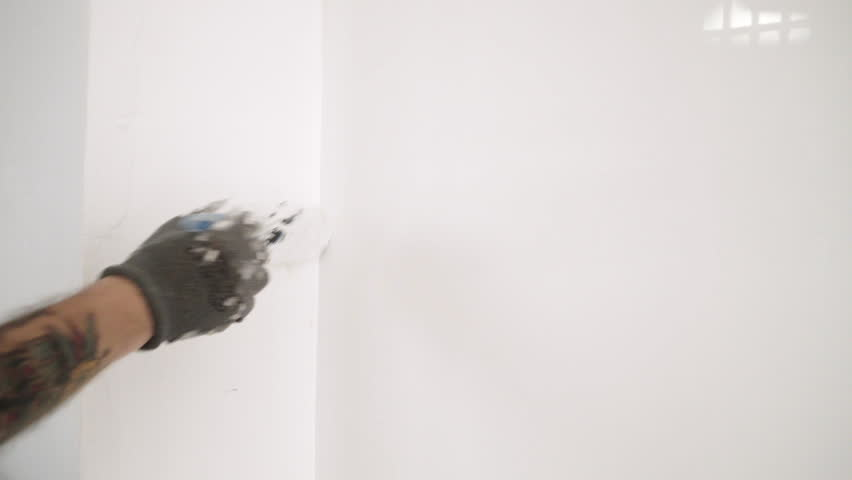 tattooed hand paints the wall in white color with brush 4k stock video clip