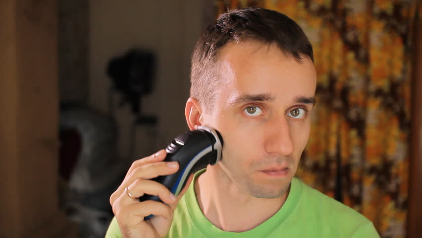 Hndsome young man shaving with electric razor. Electric shaver in living room #18039712