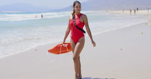 Woman in lifeguard outfit on beach with swimmers