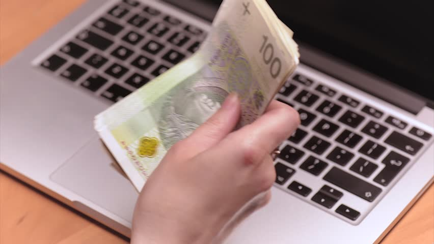 Close up of female hands counting Polish money banknotes at the table in front a laptop computer. Woman accountant with money zloty and notebook.