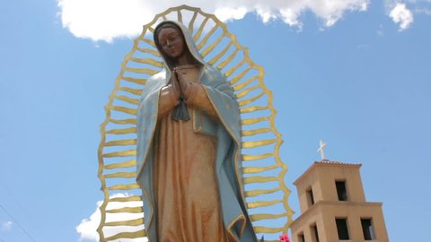 Low angle shot of a statue of the virgin of Guadalupe standing serenely in front of an adobe church. Blue sky with clouds is in the background behind the religious icon and the adobe Catholic church.