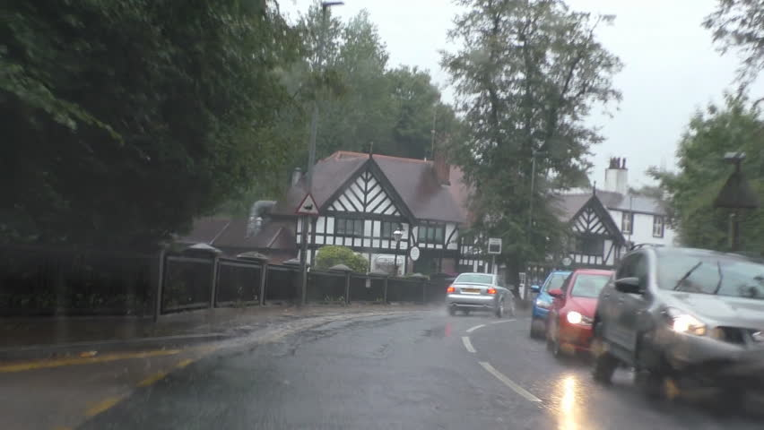 Driver POV while driving on busy road in the rain in English town of Worsley, Salford, Greater Manchester, UK
