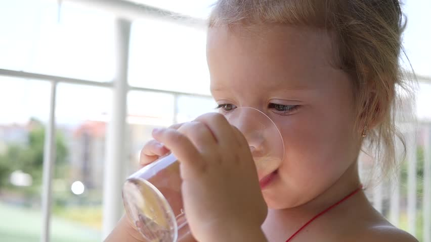 Cute child girl drinking a cup water with piece of lemon - healthy body care