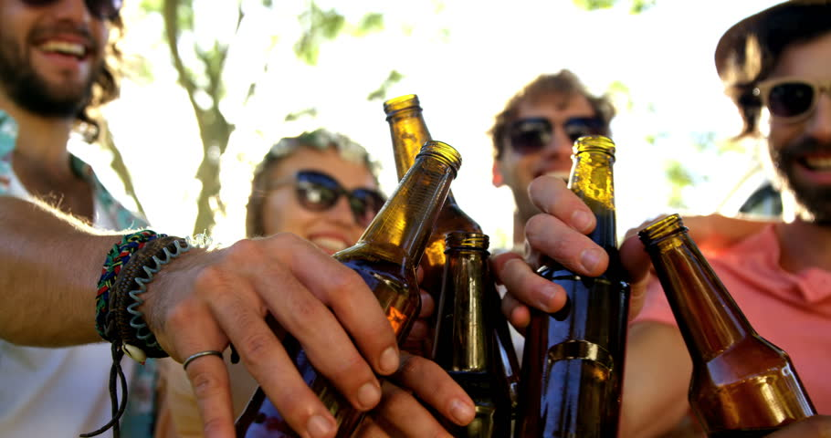 Group of hipster friends toasting together at a music festival