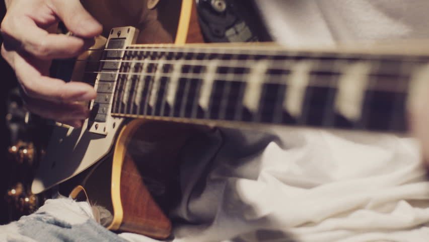 Musician playing electric guitar melody. Details of the strings and right hand near the pickups.