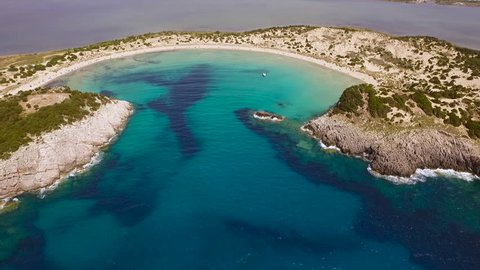 Aerial view from the popular Voidokilia beach in Peloponnese, Greece. A half-moon-shaped beach surrounded by vivid water in an unrealistic way. Slow rising motion.