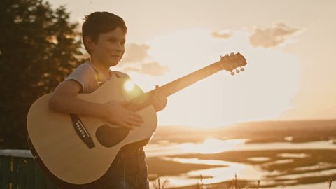 Kid having fun and play guitar at summer sunset, on high hill