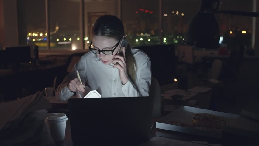 Young businesswoman sitting at desk in dark office, talking on mobile phone and eating noodles from box with sticks, open laptop in front of her, medium shot on Sony NEX700 + Odyssey 7Q