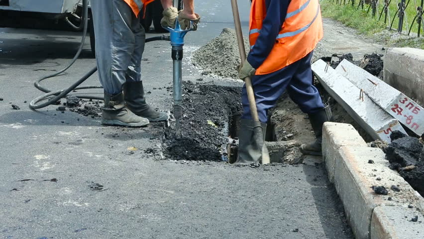 Worker Drilling Concrete With Compressor On The Street
