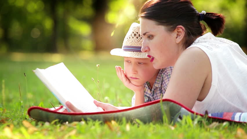 A son with his mum lying in the park on the cover reading a book | Shutterstock HD Video #18197122