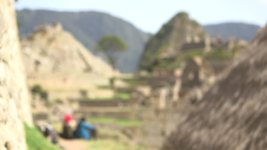 Rack focus reveal of Machupicchu ruins and tourist resting