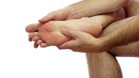 Closeup of an anonymous man isolated on a white background and rubbing his sore and painful foot and toes.