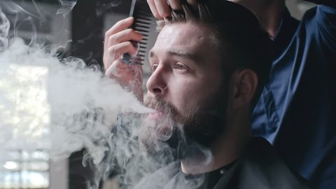Young man sitting in barber chair and vaping while hairstyling brushing his hair with comb
