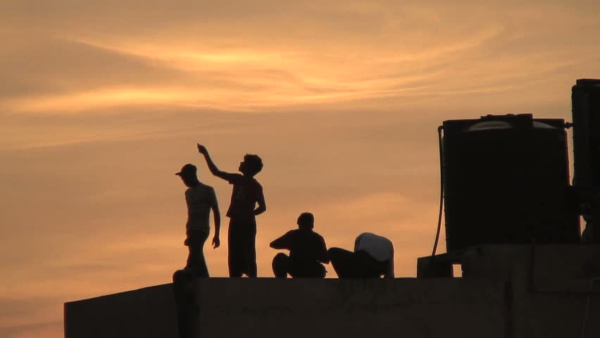 NEW DELHI, INDIA- AUGUST 7, 2006: Kids fly kites at dusk from a rooftop in New Delhi, India