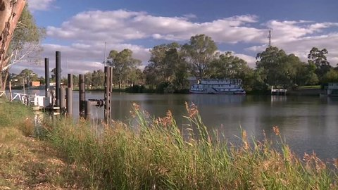 Wide shot of the river Murray at Mildura in Victoria, Australia with river reeds and a paddle steamer on the opposite bank.